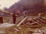 """RO"" Miller (gray hat, center), son-in-law Larry Pearce (red hat), and his brother Carl Pearce (white shirt, right)  Bridge project to Larry's new house, Oct. 1974"